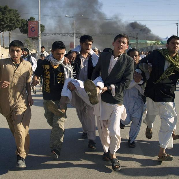 Afghans carrying a wounded man following an attack on UN's office in Mazar-e-Sharif, Afghanistan (AP)