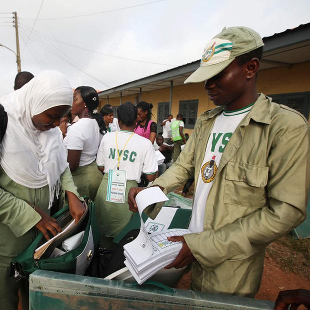 Electoral officials check ballot material at the distribution centre in Ibadan, just before the election was postponed (AP)