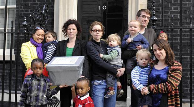 A group of parents and toddlers hand in a petition to 10 Downing Street opposing cuts to Sure Start Children's Centres across the country