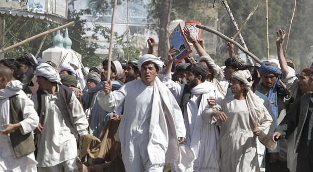 Afghan protestors walk with sticks during a demonstration to condemn the burning of a copy of the Koran (AP)