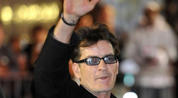Charlie Sheen waves to fans as he leaves the Chicago Theatre (AP)