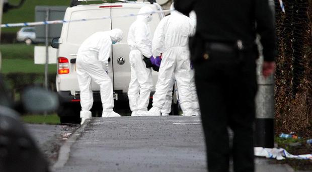 Police forensic experts examine the area where a policeman was killed in Omagh Co Tyrone