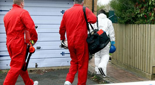 Fire investigators enter a home in Telford after the bodies of a man and a young girl were found inside