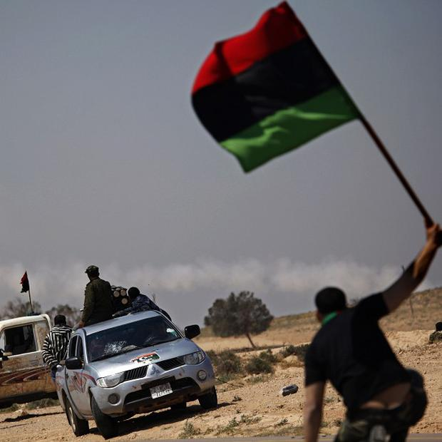 A Libyan rebel waves a pre-Gaddafi flag as other rebels fire a rocket launcher during an exchange of fire with pro Gaddafi forces along