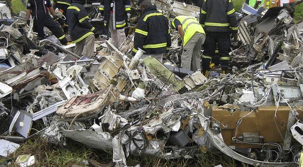 Emergency workers examine the wreckage of a UN plane that crashed as it was landing in Kinshasa, Congo (AP)