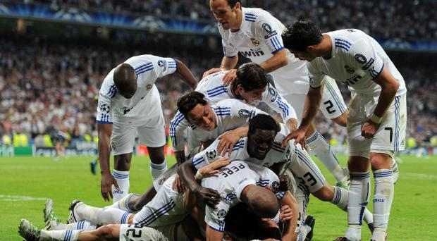 MADRID, SPAIN - APRIL 05: Real Madrid players celebrate on top of their teammate Angel Di Maria after he scored during the UEFA Champions League quarter final first leg match between Real Madrid and Tottenham Hotspur at Estadio Santiago Bernabeu on April 5, 2011 in Madrid, Spain. (Photo by Jasper Juinen/Getty Images)
