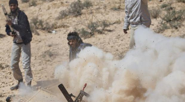 Libyan rebels fire a rocket launcher toward pro-Gaddafi forces along the front line near Brega (AP)