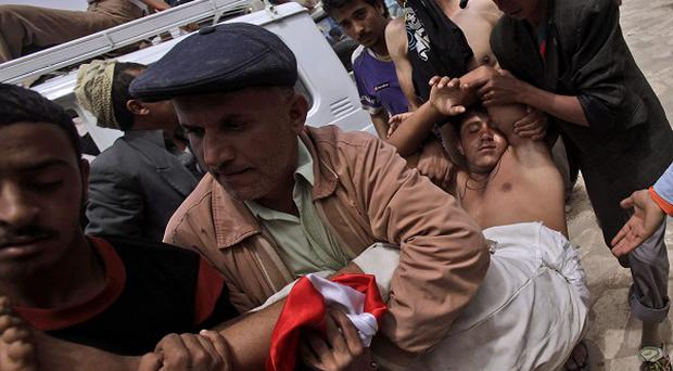 Protestors carry an injured demonstrator to a field hospital during clashes in Sanaa,Yemen (AP)