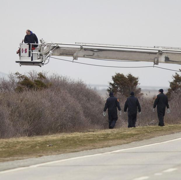 Police and fire department officers search for human remains in the brush near Oak Beach, New York (AP)