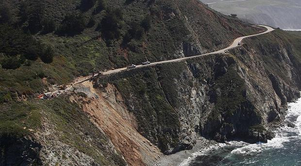 A landslide blocks Highway 1 in California after heavy weather battered the region (AP)