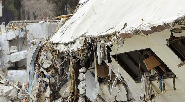 A man looks through the rubble near a building destroyed by the earthquake and tsunami in Onagawa, Japan (AP)