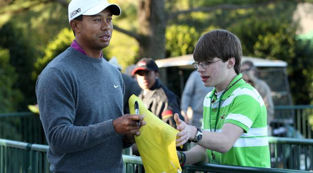 AUGUSTA, GA - APRIL 06: Tiger Woods autographs a pinflag for a fan on the practice ground during a practice round prior to the 2011 Masters Tournament at Augusta National Golf Club on April 6, 2011 in Augusta, Georgia. (Photo by Andrew Redington/Getty Images)