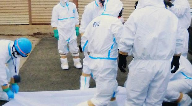 Police in protective suits with a body found after the March 11 earthquake close to Fukushima Dai-Ichi nuclear plant (AP)