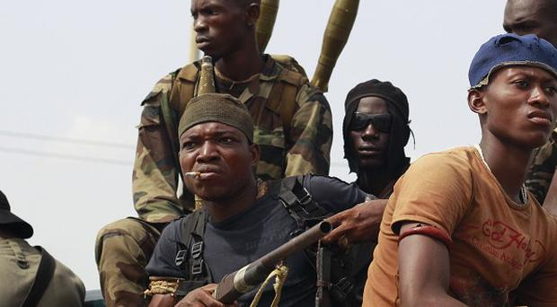 Rebels backing internationally recognised Ivory Coast leader Alassane Ouattara prepare to deploy at a checkpoint (AP)