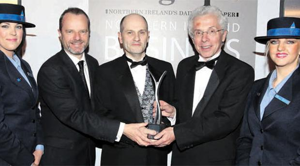 Robert Dunlop (centre) of Almac is congratulated by Mike Gilson (left), editor of the Belfast Telegraph, and Wolfgang-Prock Schauer, chief executive of British Midland International (bmi), for being named Outstanding Business of the Year at the 2011 Belfast Telegraph Northern Ireland Business Awards in association with bmi