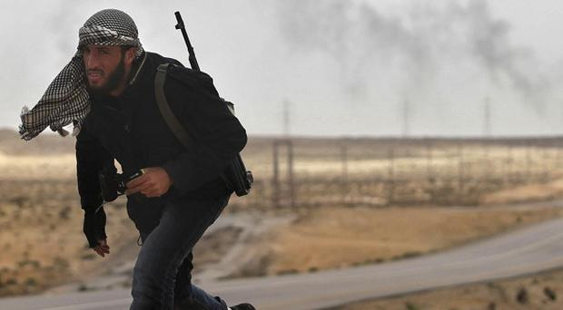 A Libyan rebel runs back for safety as shells explode in the distance on the frontline near Brega (AP)
