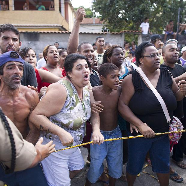 Residents gather outside a school in Rio de Janeiro where a shooting spree left 11 dead (AP)
