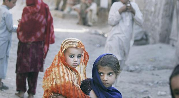 Afghan refugee children gather in an alley of a slum on the outskirsts of Islamabad (AP)