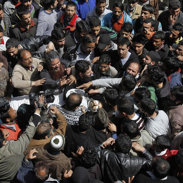 Kashmiri Muslims crowd around the body of Moulvi Showkat Ahmed Shah (AP)