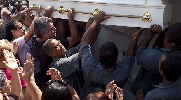 Mourners lift the coffin carrying 13-year-old Laryssa Silva, one of the victims of the Rio de Janeiro school shooting (AP)