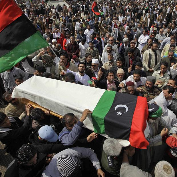 A coffin is carried away after a funeral for some of those killed by a Nato air strike on rebel forces in Libya (AP)