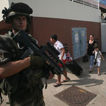 Members of the French military evacuate French nationals and other foreigners from a hotel in Abidjan , Ivory Coast (AP)