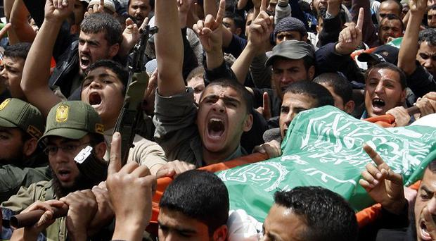 Palestinians carry the bodies of Hamas militants killed on Thursday's attack on Gaza (AP)