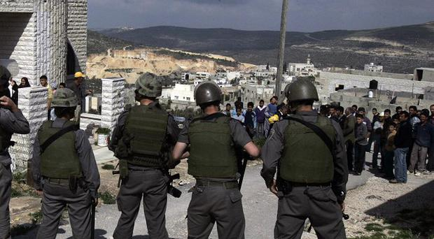 Israeli troops arrive to break up a scuffle between Jewish settlers and Palestinians in the West Bank village of Aseera (AP)
