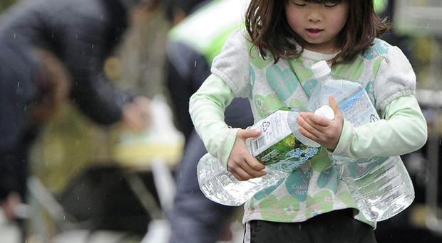 A girl carries bottles of water collected in Ofunato, northern Japan (AP Photo/Kyodo News)