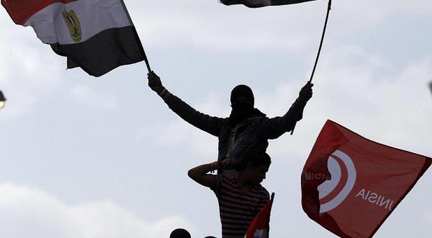 Protesters wave Egyptian and Tunisian flags as they attend a rally in Tahrir Square, Cairo (AP)