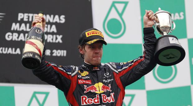 Red Bull Formula One driver Sebastian Vettel of Germany holds his trophy aloft after winning the Malaysian Formula One Grand Prix in Sepang, Malaysia, Sunday, April 10, 2011