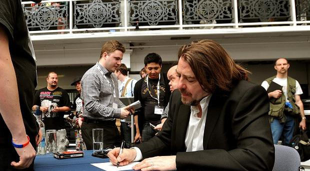 Jonathan Ross signs an autograph at the Kapow Comic Convention at the Design Centre in Islington