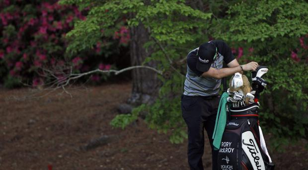 Rory McIlroy of Northern Ireland leans on his golf bag on the 13th hole during the final round of the Masters golf tournament Sunday, April 10, 2011, in Augusta, Ga