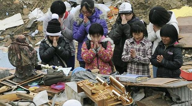 Survivors take a moment of silence in the rubble exactly a month after a massive earthquake struck Japan (AP/Kyodo News)