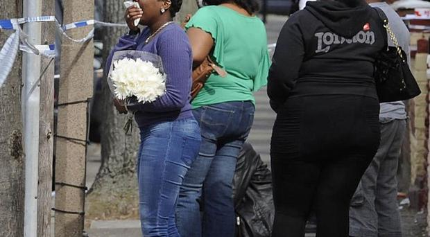 A relative waits to lay flowers at the scene of a boy's fatal stabbing in Edmonton, north London (PA)