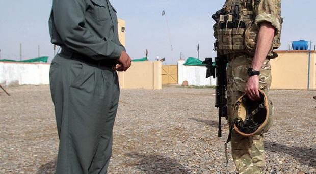 Major Nick Wight-Boycott talks to an Afghan National Police commander in a compound next to Patrol Base Attal in Helmand Province