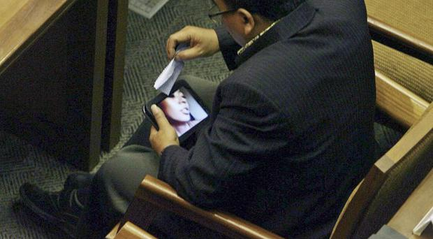Indonesian parliament member from Prosperous Justice Party Arifinto watches a porn video on his tablet computer (AP)