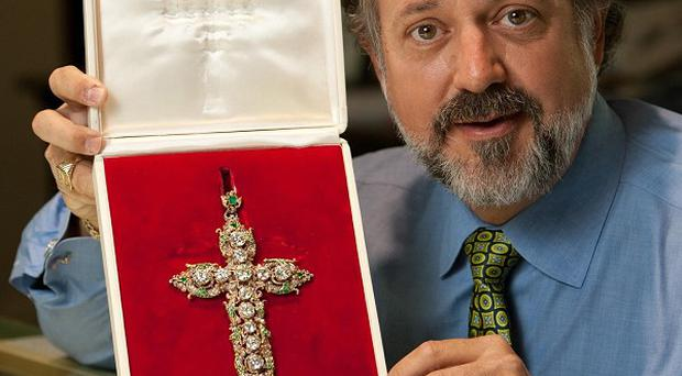 Alan Perry displays the papal jewellery he will be selling on eBay (AP)