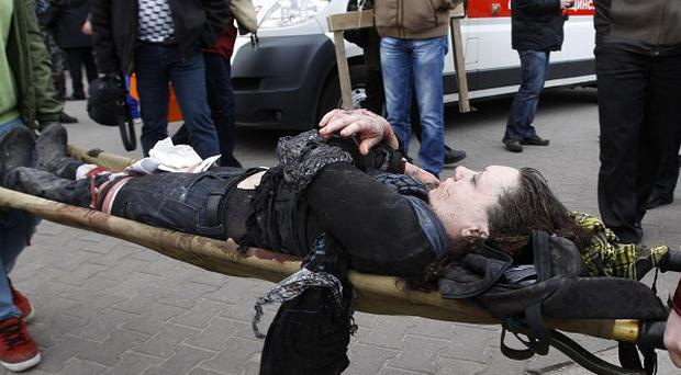 An injured blast victim is brought by rescuers to an ambulance in Minsk, Belarus (AP)