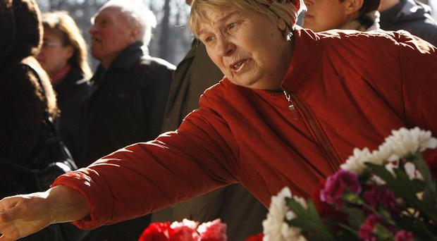 A woman places flowers at an entrance to the Oktyabrskaya station of the Minsk subway network after a bomb attack (AP/Sergei Grits)