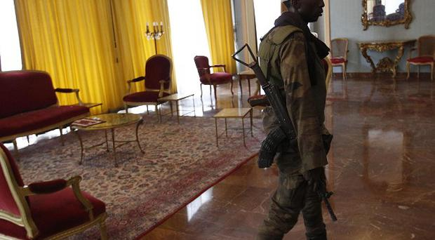 A republican forces soldier walks through a sitting room at the presidential palace in central Abidjan, Ivory Coast (AP)