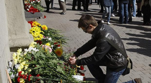 A man lights a candle at an entrance to the Oktyabrskaya station of the Minsk subway network after a bomb attack which claimed 13 lives (AP/Sergei Grits)
