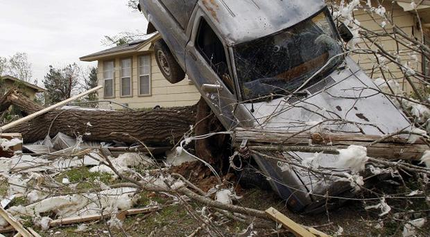 A vehicle rests on a tree after a tornado in Tushka, Oklahoma (AP)