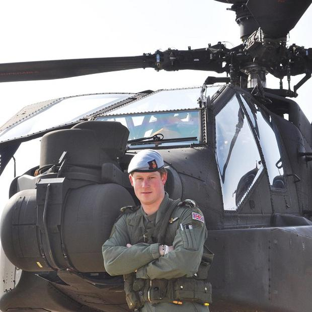 Prince Harry, now Captain Harry Wales, in front of his Apache Helicopter