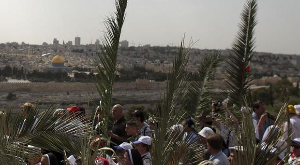 Christian pilgrims participate in the traditional Palm Sunday procession on the Mount of Olives, overlooking Jerusalem's Old City (AP)
