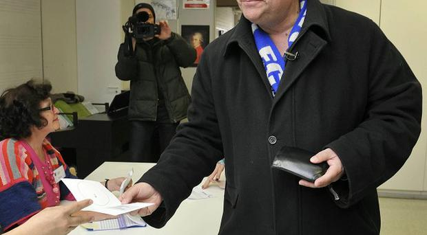 Timo Soini, leader of the opposition True Finns party, casts his vote in Finland's parliamentary elections (AP)