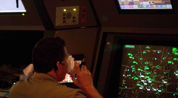 An air traffic controller drinks a cup of coffee while working in a terminal radar approach control room (AP)