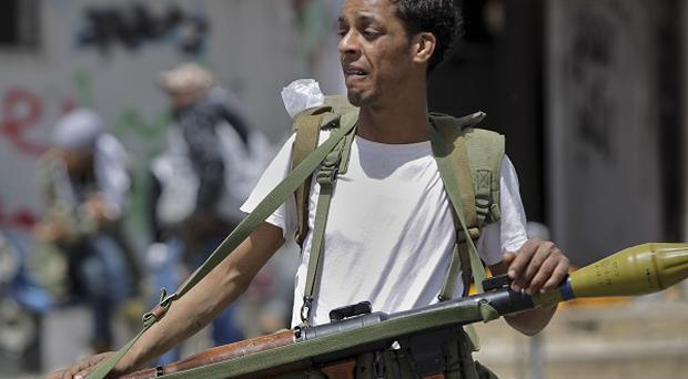 A Libyan rebel fighter looks toward the front line, on the outskirts of Ajdabiya, Libya (AP)