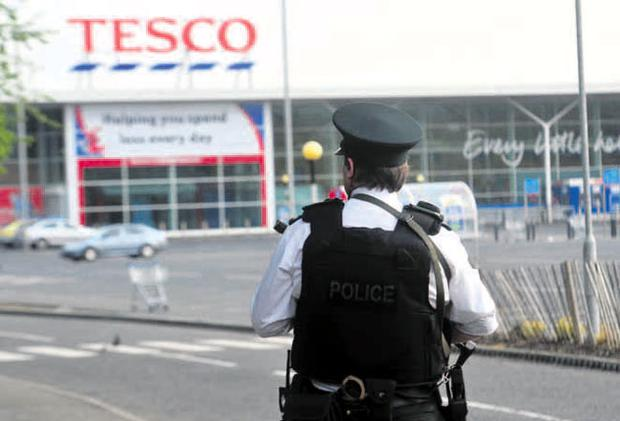 Police at the scene of the stabbing at Tesco in Ballygomartin, north Belfast