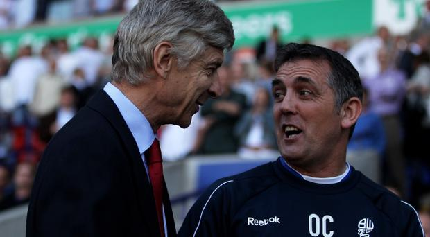 BOLTON, ENGLAND - APRIL 24: Arsenal Manager Arsene Wenger chats with Bolton Wanderers Manager Owen Coyle (R) prior to the Barclays Premier League match between Bolton Wanderers and Arsenal at the Reebok Stadium on April 24, 2011 in Bolton, England. (Photo by Michael Steele/Getty Images)